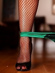Danica in emerald green corset and panties with fishnet stockings.